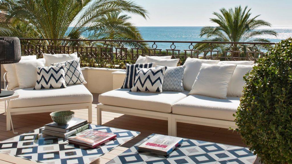 Terraza zona chill out con muebles blancos y plantas