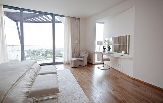 Habitación amplia en tonos blancos y suelo de madera, con tocador y sillones.