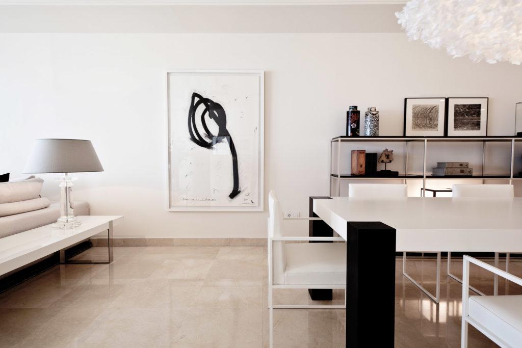 salón estilo minimalista en tonos blancos con elementos decorativos en negros