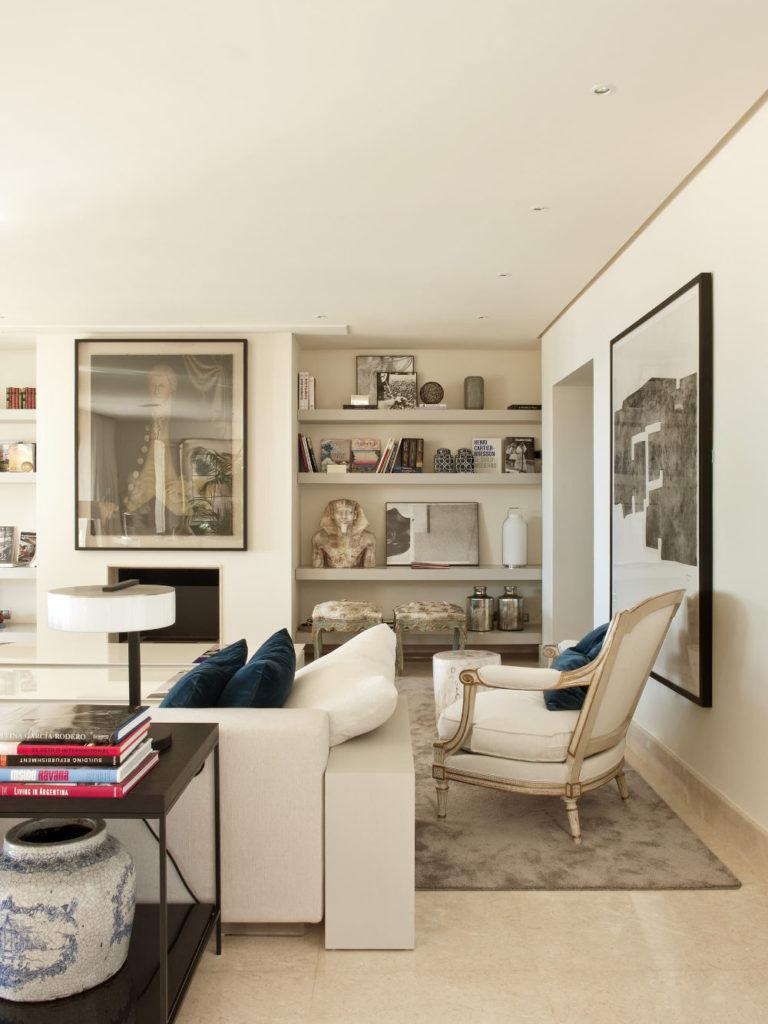 salón con una estantería con piezas de artesanía como esculturas y jarrones.